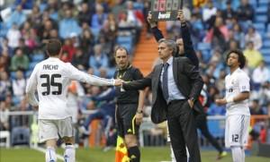 Nacho takes to the field as Mourinho looks on.